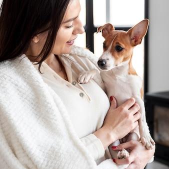 Вид сбоку женщины, держащей ее собаку