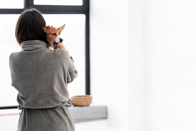 彼女の犬を保持しているバスローブの女性の背面図