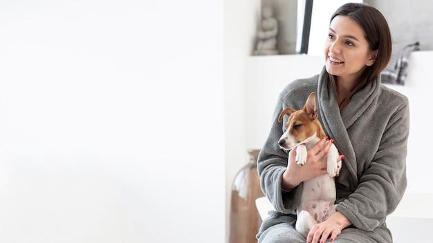 Улыбающаяся женщина в халате держит собаку