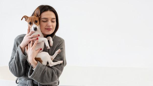 彼女の犬を保持しているバスローブの女性の正面図
