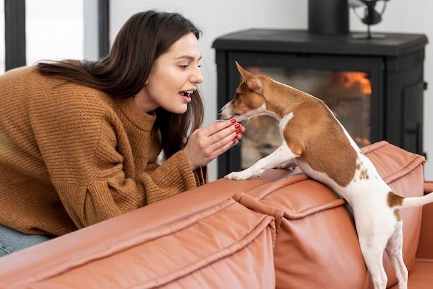 リビングルームで彼女の犬をかわいがる女性