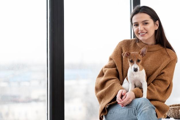 Женщина позирует, держа собаку на коленях