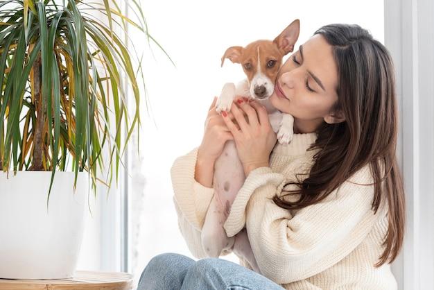 彼女のかわいい犬を抱きしめる女性