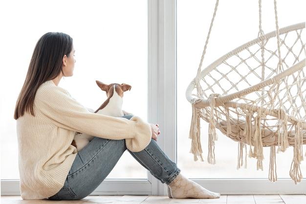 ハンモックの横にある彼女の犬を持つ女性の側面図