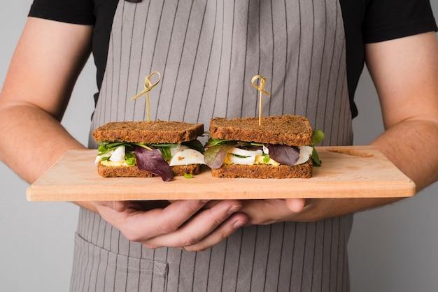 サンドイッチと木の板をホールド男