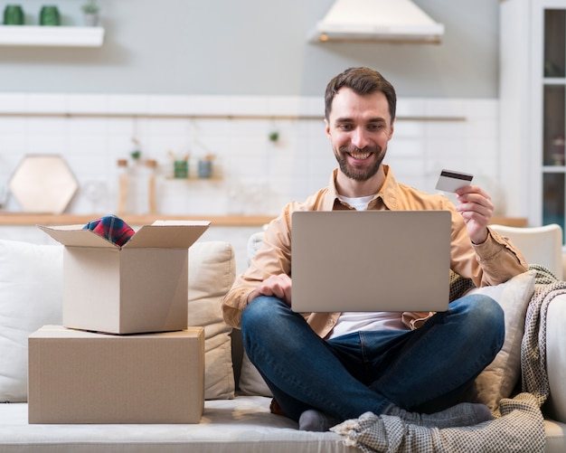 Смайлик мужчина заказывает онлайн с помощью кредитной карты на ноутбуке