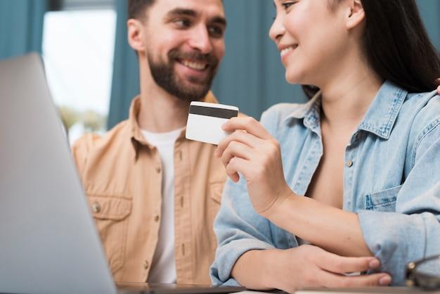 幸せなカップルは、ラップトップとクレジットカードを使用してオンラインショッピング