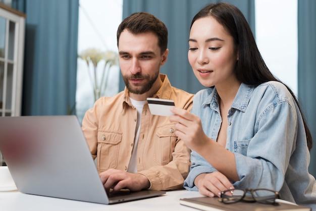 ノートパソコンで男性にクレジットカード情報を口述する女性