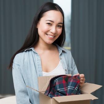スマイリー女性がオンラインで注文したボックスでポーズ