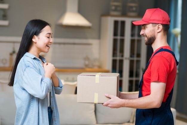 Доставка человек дает коробку женщине, которая заказала онлайн