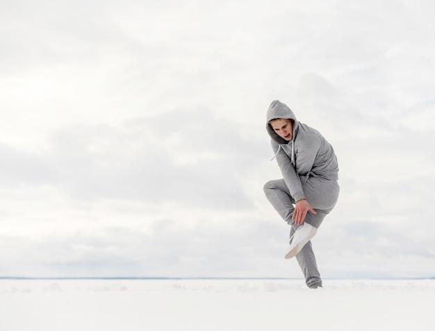 コピースペースで雪の中で踊るヒップホップアーティストの側面図