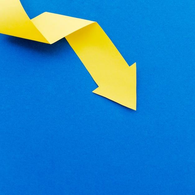 Вид сверху желтой бумажной стрелки с копией пространства
