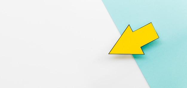 Высокий угол желтой бумаги стрелка с копией пространства