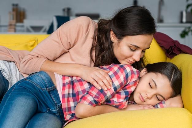 母と娘がソファに座って