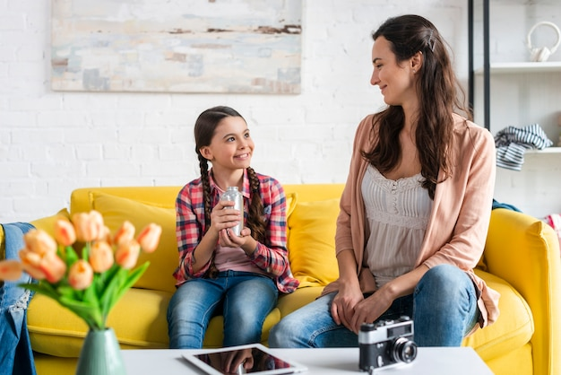 Мать и дочь, сидя на желтом диване