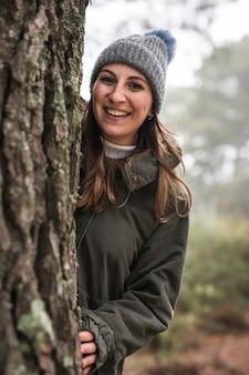 木の後ろにミディアムショットの女性