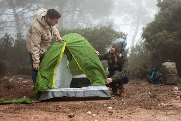 緑のテントを置くミディアムショットカップル