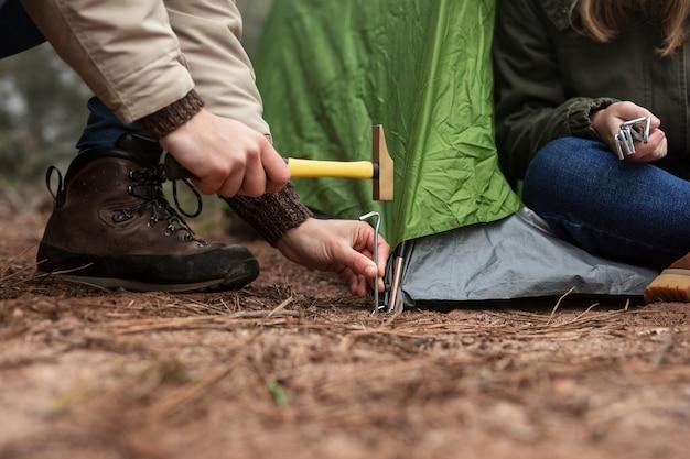 緑のテントを置くクローズアップの人々