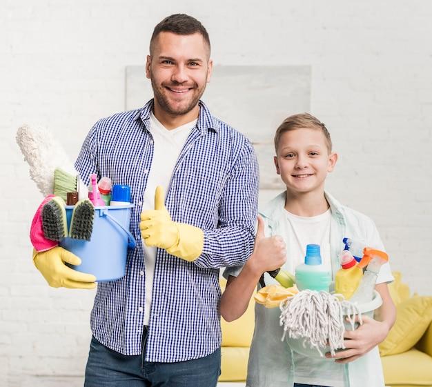父と息子のクリーニング製品を保持しながら親指をあきらめる