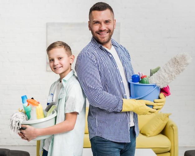 スマイリーの父と息子が掃除しながら背中合わせにポーズ