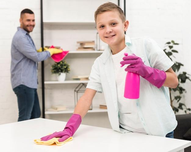 ゴム手袋で掃除しながらポーズをとってスマイリー少年