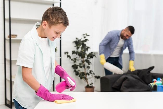 父親に沿って家を掃除する少年の側面図