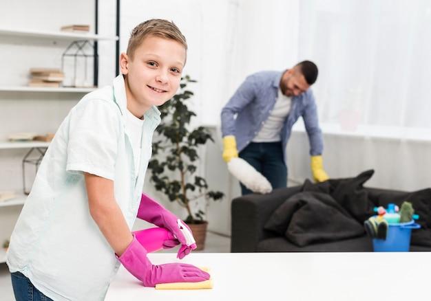 掃除しながらポーズをとって笑顔の少年の側面図