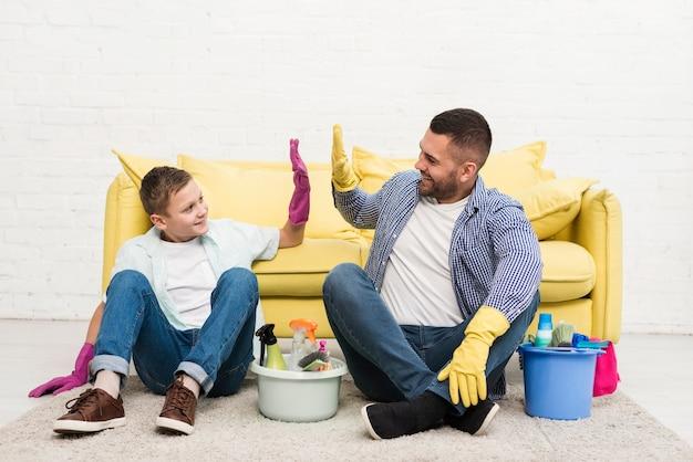 清掃中の父と息子のハイファイブ