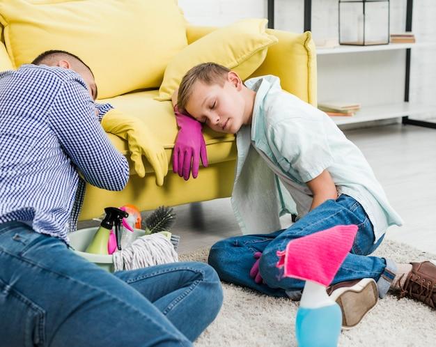 掃除の後寝ている息子と父親