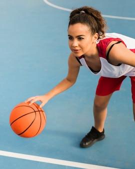 Высокий угол девушка играет в баскетбол