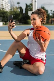 Вид спереди девушки, принимая селфи с баскетбольный мяч