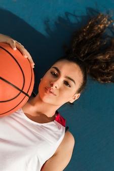 Вид спереди девушки с баскетбольным мячом
