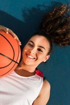 バスケットボールボールで微笑んでいる女の子の正面図