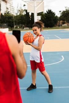 バスケボールでポーズの女の子の完全なショット