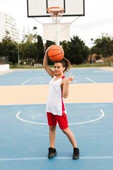 バスケボールでポーズの女の子のロングショット