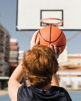 Взгляд конца-вверх мальчика играя баскетбол