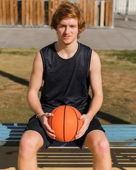 バスケットボールを保持している少年の正面図
