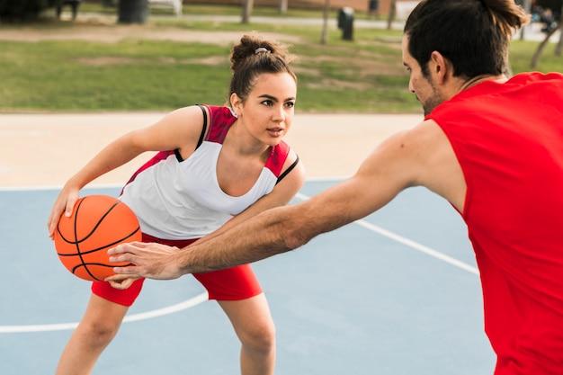 Мальчик и девочка играют в баскетбол
