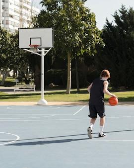 Длинный выстрел мальчика, играющего в баскетбол