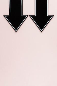 コピースペースとピンクの背景に下向きフラットレイアウト黒矢印