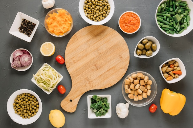 Вид сверху разделочной доски с острым перцем и зеленым горошком