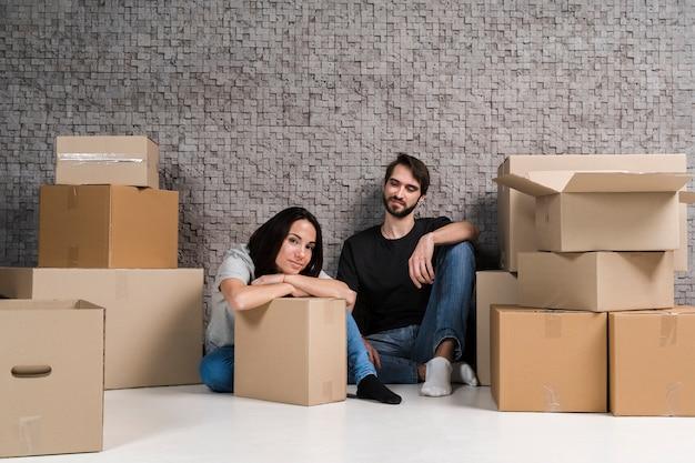 若い男性と女性の移転のためのボックスの準備
