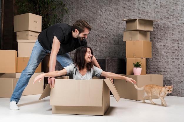 Симпатичный молодой мужчина и женщина празднуют переезд