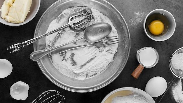 Вид сверху миску с мукой и яйцами на столе