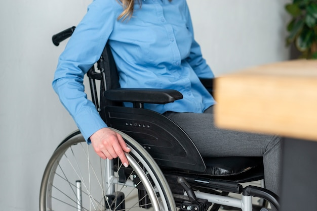 Крупным планом женщина в инвалидной коляске в офисе