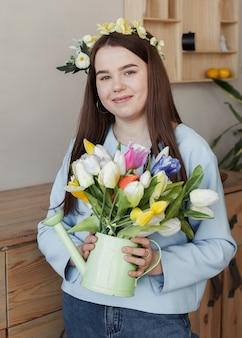 花と水まき缶を保持している若いかわいい女の子
