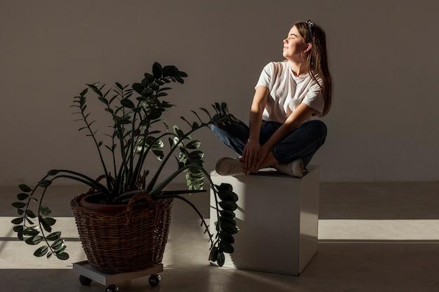 Молодая девушка сидит в тени и растений