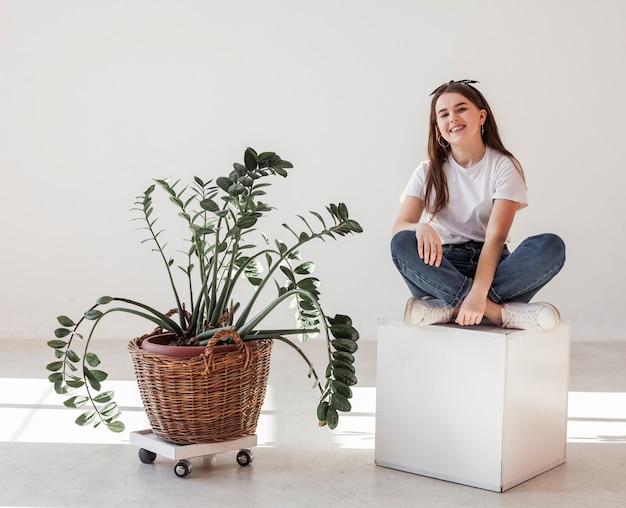 Молодая девушка и домашнее растение