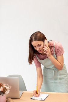 電話で話しているとメモを取るビジネス女性