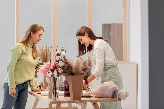 Боком деловые женщины устраивают цветочный магазин
